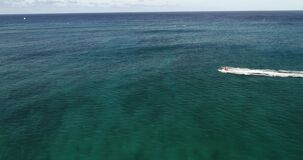 Flying POV, life guard on jet ski performing rescue operation off the coast of, Maui, Hawaii, in deep blue water _