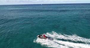 Aerial view, life guard on jet ski performing rescue operation off the coast of, Hawaii, in aquamarine water _