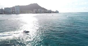 Slow motion, Drone footage, life guard on jet ski performing rescue operation off the coast of, Hawaii, in blue water _
