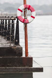The Rescue Hoop. Life buoy hanging on a post at the pier by the riverside stock photos