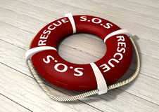 Rescue Lifebuoy. An red lifebuoy with the rope around it and the words sos and rescue on a sunbleached wooden background stock photos