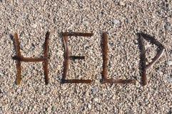 Rescue message. Om a stone beach stock photos