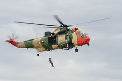 Rescue Operation. Man hanging on the winch of the rescue helicopter Stock Photo