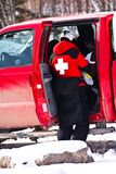 A rescue patrol officer pulling something out of t. A rescue patrol officer in alert pulling something out of the vehicle at a ski resort Royalty Free Stock Images