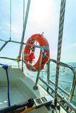 Rescue red lifebuoy life preserver saver ring on sailboat. Yachting in summer time Royalty Free Stock Image