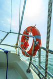Rescue red lifebuoy life preserver saver ring on sailboat. Yachting in summer time Stock Image