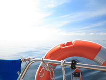 Rescue red lifebuoy on sail and blue sky sea. Safe water support aid circle. Rescue red lifebuoy life preserver saver ring on sailboat and blue sky baltic sea Royalty Free Stock Images