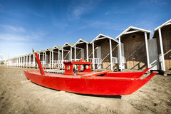 Rescue red rowing boat. Huts wooden on the beach. Royalty Free Stock Photos