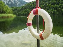 Rescue ring at the Swan Lake in Bavaria. Mast with rescue ring at the Swan Lake geman language: Schwansee at bavaria in summer 2017 Stock Photos