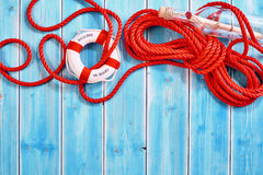 Rescue rope with life preserver and bottle. Partially unraveled red rescue rope and ring shaped life preserver beside message in a glass bottle over weathered Royalty Free Stock Photography