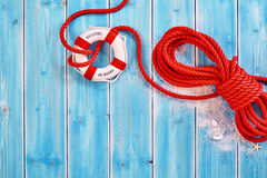 Rescue rope with life preserver over blue. Red colored thick rope with loose knot around ringed white life preserver over blue wood paneling with sand, seashells Royalty Free Stock Photo