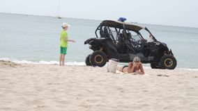 Rescue service buggy monitors the security of people on the beach of Dadonghai stock footage video. Sanya, China - April 02, 2017: Rescue service buggy monitors stock video footage