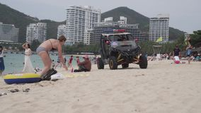 Rescue service buggy monitors the security of people on the beach of Dadonghai stock footage video. Sanya, China - April 02, 2017: Rescue service buggy monitors stock video