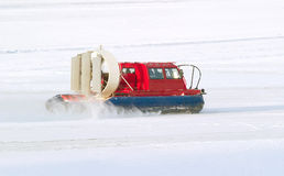 Rescue Service snowmobile patrol on duty in winter. On frozen north river Royalty Free Stock Photo