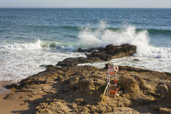 Rescue station on the beach. With a wave-busting in the rock as background Royalty Free Stock Photography