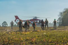 Rescue team carrying injured paasenger to helicopter to hospital stock photography