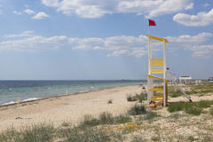 Rescue tower with a red flag on the beach of the resort village Vitino in the Saksky district of the Crimea Stock Photo