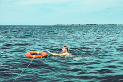 Rescue on waters. A guy and a life ring in the sea Stock Photos