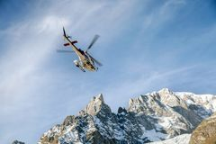 A rescue helicopter over mountains stock photo