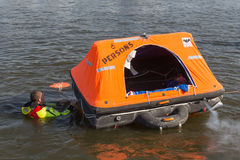 Rescue worker showing life raft in harbor Urk, the Netherlands Royalty Free Stock Photo