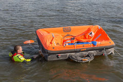 Rescue worker showing life raft in harbor Urk, the Netherlands Royalty Free Stock Image