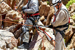 Rescue Workers practicing a Rescue Drill on Ledge of Mountain Stock Images