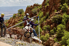 Rescue Workers practicing a Rescue Drill on Ledge of Mountain Stock Image