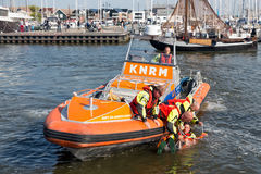 Rescue workers showing how to save people out of water. URK, THE NETHERLANDS - SEP 24: Rescue workers at lifeboat showing how to save people out of the water on royalty free stock photo