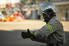 Rescuer and burning car Stock Photography