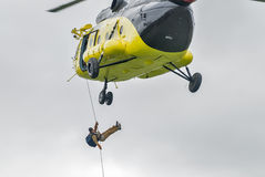 Rescuer is landed from MI-8 helicopter by rope Stock Photos