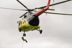 Rescuer is landed from MI-8 helicopter by rope Royalty Free Stock Photography