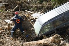 Rescuer removes debris from the car Royalty Free Stock Image