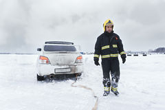 Rescuer standing at the stuck car Royalty Free Stock Images