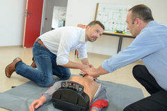 Rescuer teaching man how to proceed during traineeship Stock Photography