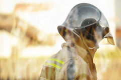 Rescuer view through flames. Rescuer in helmet and uniform profile view through flames firefighting concept Royalty Free Stock Images