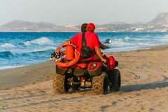 Rescuers on ATV on the beach. At sunset, Crete, Greece royalty free stock image