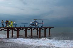 Rescuers head for a helicopter, in a gale. Night time.  stock photo