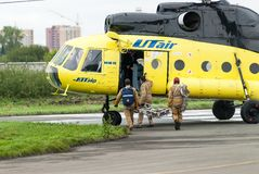 Rescuers load into helicopter MI-8 Royalty Free Stock Image