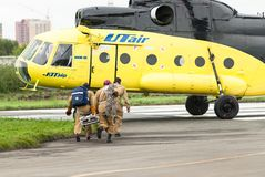 Rescuers load into helicopter MI-8 Stock Photos