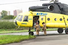 Rescuers load into helicopter MI-8 Royalty Free Stock Images
