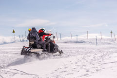 Rescuers on snowmobiles in the mountains. Rescuers on snowmobiles in the snowy mountains Royalty Free Stock Images