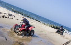 Rescuing a quad (ATV). Two quads, one is pulling the other from wet sand. (ATV Royalty Free Stock Photos