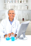 Reseacher in Laboratory. Researcher seated in laboratory setting with beakers of liquid and computer monitor. Vertical format Stock Photos