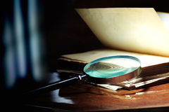 Research. Old book and magnifier glass on a dark background as a symbol of knowledge and science Stock Photo