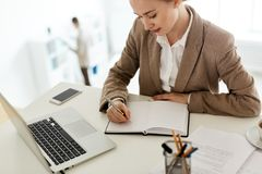 Research of analyst. Young accountant making notes in notebook while preparing for seminar stock image