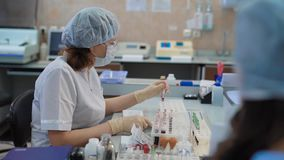 Research assistant dressed in white lab coat, protective spectacles, mask, cap and gloves sitting at the table with a. Research assistant dressed in white lab stock video footage
