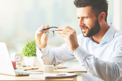Research concept. Attractive caucasian businessman looking at laptop screen throught spectacle lenses. Research concept stock photo