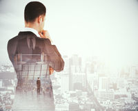 Research concept. Back view of thoughtful young businessman on abstract city background. Research concept. Double exposure Stock Photo