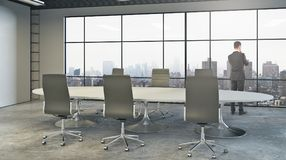 Research concept. Back view of thoughtful young businessman looking out of window in modern conference room with equipment and city view. Research concept. 3D Stock Photo
