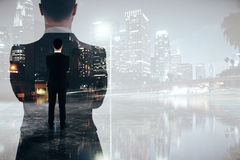Research concept. Back view of young businessman and silhouette on creative city background with copy space. Research concept. Double exposure Stock Photo